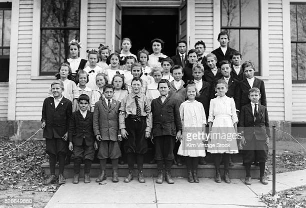 Students of a one room school house pose on the the steps of their school for a group portrait