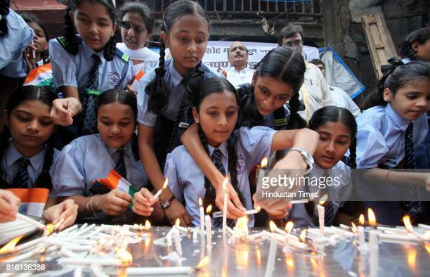 Students of Barretto High School from Kalbadevi light candles to pay homage to the victims of Mumbai bomb blasts at Zaveri Bazar one of the three...