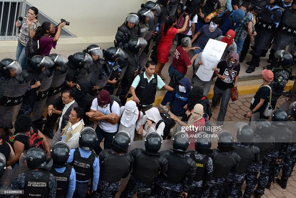 Students of the National Autonomous University of Honduras (UNAH), demanding of changes to the education system, are protected from the National Police by members of Human Rights organizations, as they evacuate the University building at the end of 31 days of occupation, in Tegucigalpa on July 1, 2016. / AFP / ORLANDO
