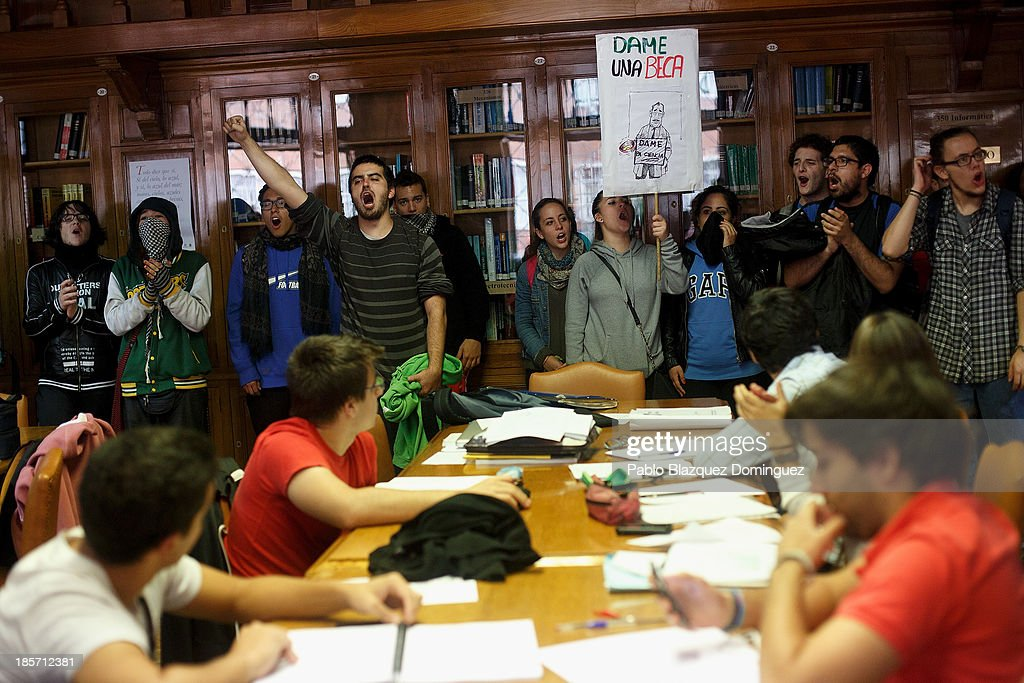 Students on strike enter shouting slogans and holding a placard reading 'give me a scholarship' at the library of School of Aeronautic Engineers in Ciudad Universitaria on October 24, 2013 in Madrid, Spain. The Spanish Parliament recently approved a controversial reform of the educational system, which passed by the ruling right wing People's Party (PP) using their absolute majority and not backed by any other political party. The students are on a three day strike to protest against the new law, which will need to be approved by the senate next month and are calling for the resignation of Education Minister, Jose Ignacio Wert.