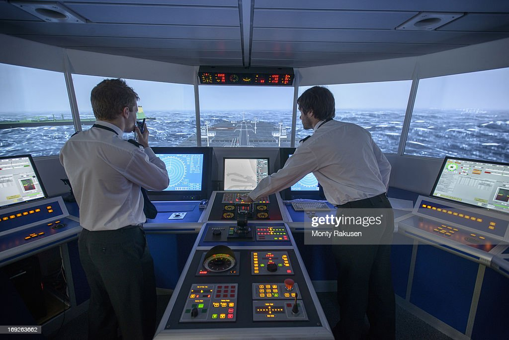 Students operating equipment in ship's bridge simulation room