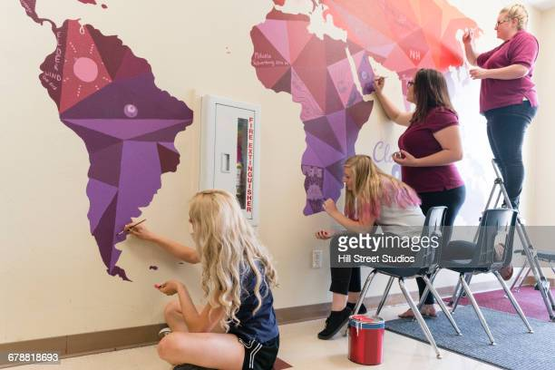 Students painting mural of map on school wall