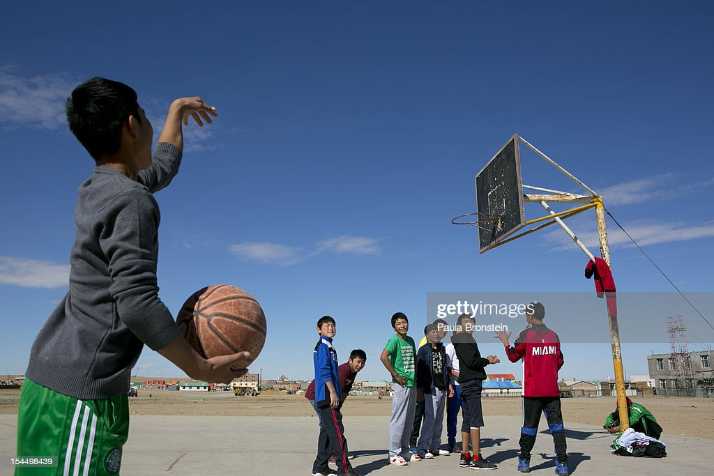 Students play basketball on a new court built by Oyu Tolgoi during a physical education program at the Khanbogd Secondary school on October 13, 2012 in Khanbogd, Mongolia. The population of Khanbogd has doubled in the last few years along with the secondary school adding a new extension to accommodate the growing number of students since Oyu Tolgoi employs most of the people in the town.The Oyu Tolgoi copper and gold mine (translated means Turquiose Hill) is a combined open pit and underground mining project. While the construction continues open pit mining is currently underway with full production expected later in 2012. When the mine starts full operation the country will be set to become one of the world's top copper and gold producers with estimates of 450,000 tons of copper and 330,000 ounces of gold. Financing for the project has come in part from the Rio Tinto Group and an investment agreement between Ivanhoe Mines and the government of Mongolia. Mongolia's largest foreign investment project to date which is projected to add one-third of future value to the country's GDP. Many estimate Mongolia to be the world's fastest growing economy with an estimated $1.3 trillion in untapped mineral resources.