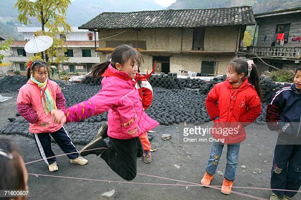 Students play outside of their primary school next to coal in Fengjie Sichuan province December 5 2005 The buildings in the background are a store...