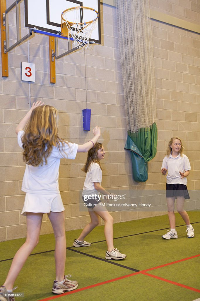 Students playing basketball indoors : Stock Photo