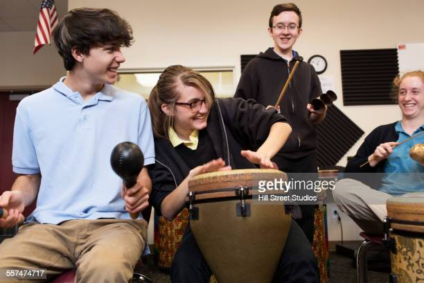 Students playing bongo drums in high school band class