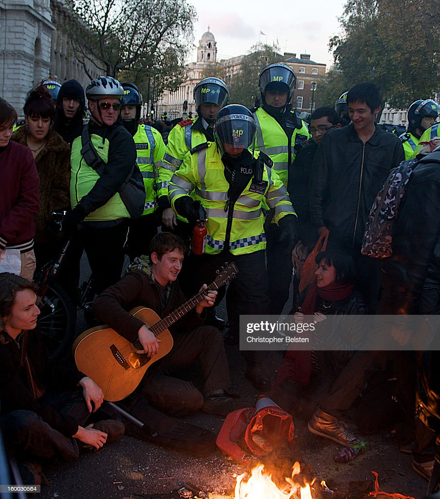CONTENT] Students playing guitar and sitting in protest on Whitehall, London during the G20 demonstrations as police attempt to extinguish fire