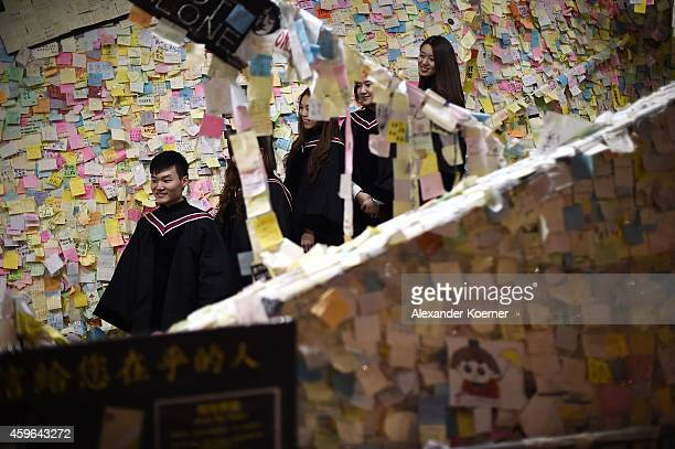 Students pose for a photograph in front of a collage of 'Postits' hung up by prodemocracy protesters and other supporters at the protest camp at...