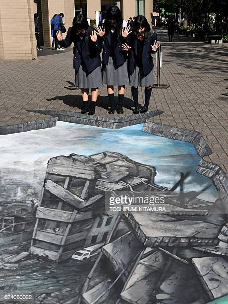 Students pose for a picture with a 3D optical illusion artwork of a devastated cityscape in Aleppo Syria at the campus of the Meiji University in...