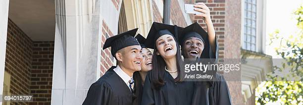 Students posing for cell phone selfie at graduation