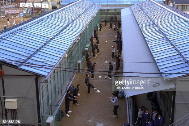 Students practice football between temporary school buildings at Takasho Junior High School on January 10 1996 in Kobe Hyogo Japan