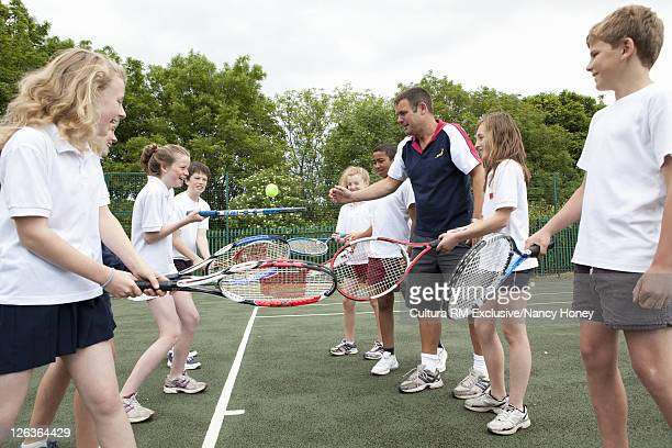 Students practicing with tennis racket