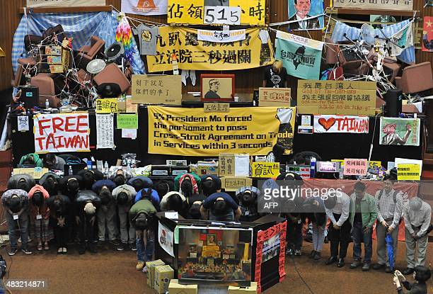 Students protest leaders Lin Feifan and Chen Weiting bow during an occupy protest against a contentious trade agreement with China inside the...