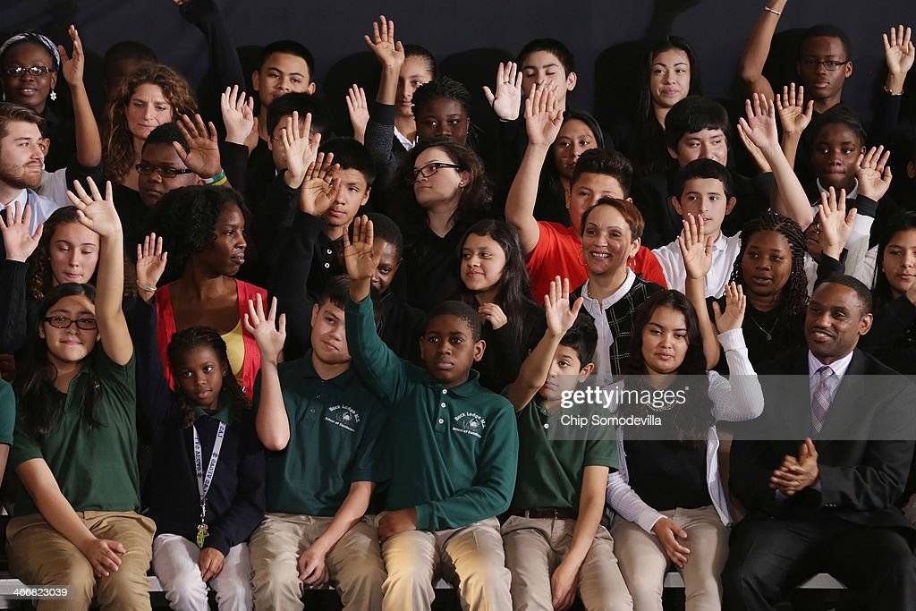 Students raise their hands when asked if they plan on going to college before the arrival of U.S. President Barack Obama at Buck Lodge Middle School February 4, 2014 in Adelphi, Maryland. As part of the president's ConnectED program, Obama has tasked the Federal Communications Commission to help to build high-speed digital connections to America's schools and libraries, with the goal of getting 99-percent of American students to next-generation broadband and wireless technology within five years.
