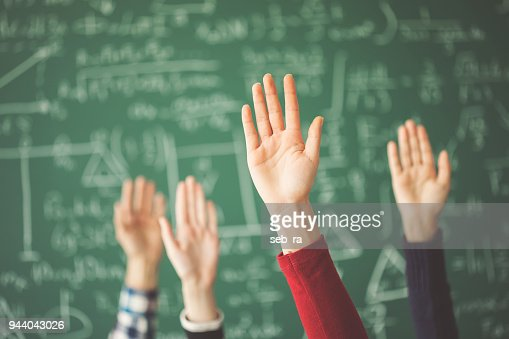 Students raised up hands green chalk board in classroom : Stock Photo