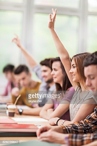 Students raising hands in the classroom.