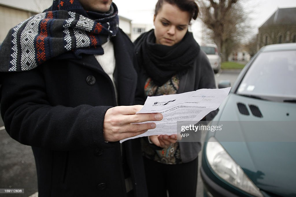 Students read a leaflet against gay marriage issued by French Apel parents' association, attached to their report card on January 8, 2013 at the Saint-Lô Catholic school in the northwestern city of Agneaux.