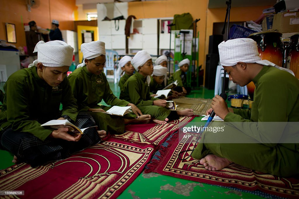 Students read copies of the Koran at the Iqro Al-Quran Bestari academy for the orphanage in the suburbs of Kuala Lumpur on November 7, 2012. AFP PHOTO / MOHD RASFAN