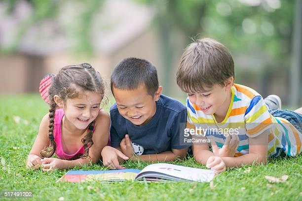 Alunos um ler um livro no parque