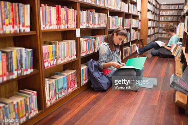 Students reading notes on floor in library