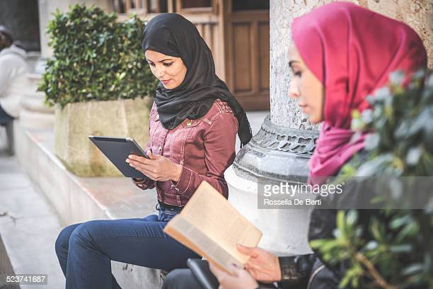 Students Reading On Paper Book And Tablet