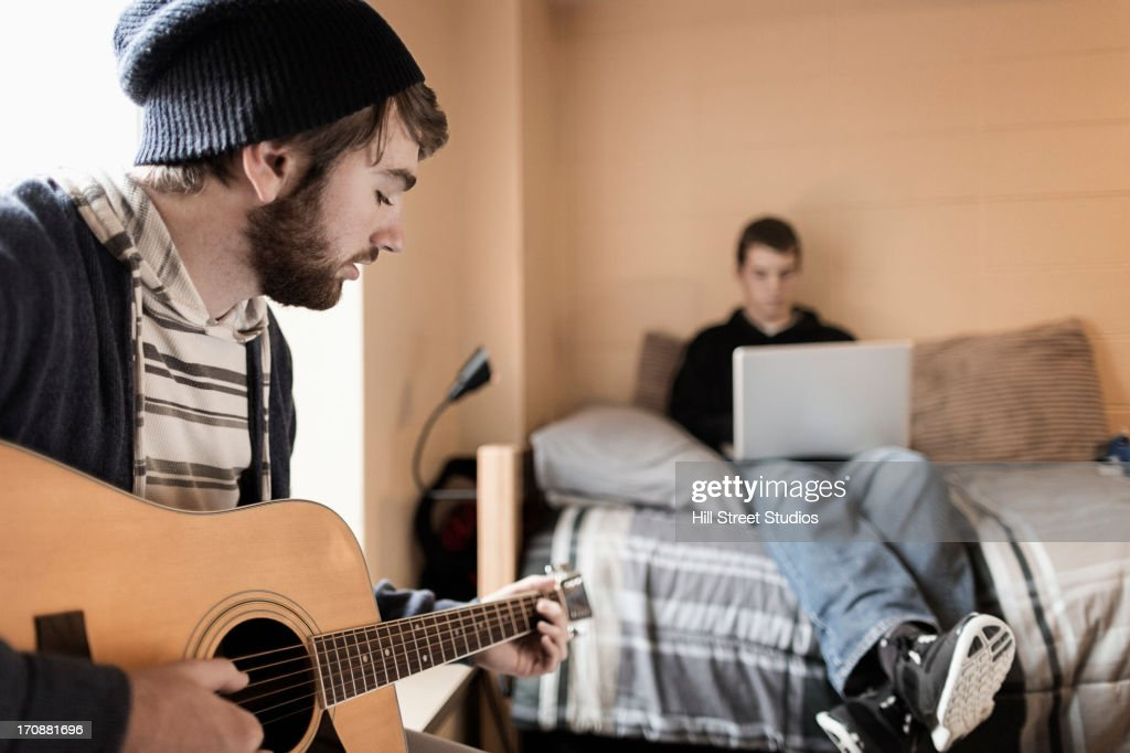 Students relaxing in dorm room : Stock Photo