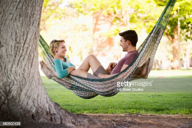 Students relaxing in hammock on college campus