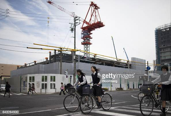 Students ride bicycles past a the construction site of a building in Toyota City Aichi Japan on Friday Oct 14 2016 Toyota Motor Corp plans to rely on...