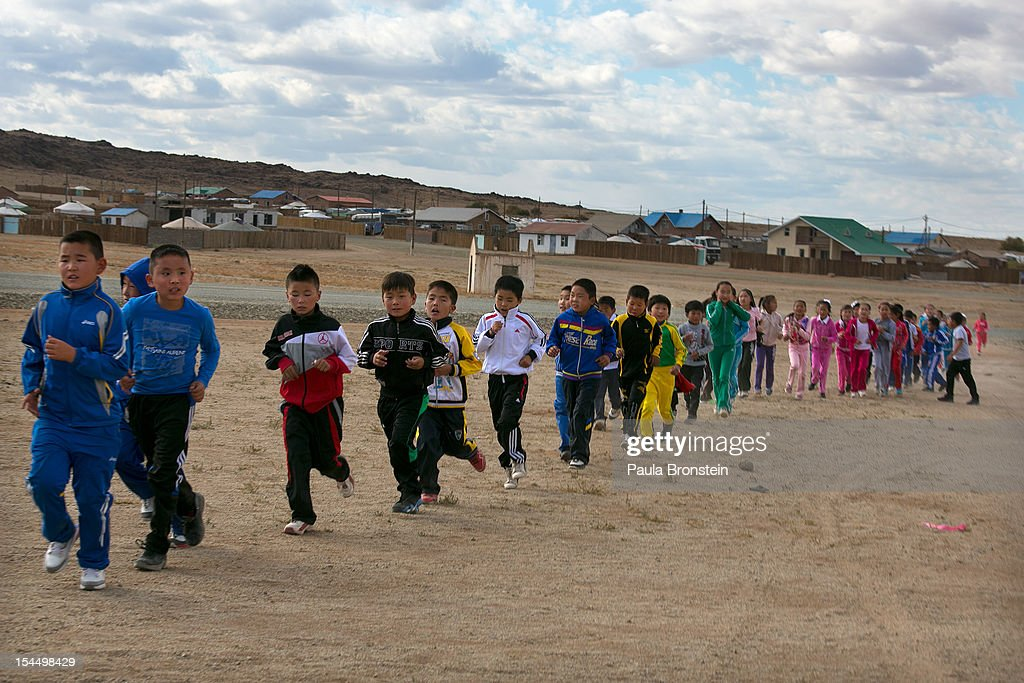Students run during a physical education program at the Khanbogd Secondary school on October 13, 2012 in Khanbogd, Mongolia. The population of Khanbogd has doubled in the last few years along with the secondary school adding a new extension to accommodate the growing number of students since Oyu Tolgoi employs most of the people in the town.The Oyu Tolgoi copper and gold mine (translated means Turquiose Hill) is a combined open pit and underground mining project. While the construction continues open pit mining is currently underway with full production expected later in 2012. When the mine starts full operation the country will be set to become one of the world's top copper and gold producers with estimates of 450,000 tons of copper and 330,000 ounces of gold. Financing for the project has come in part from the Rio Tinto Group and an investment agreement between Ivanhoe Mines and the government of Mongolia. Mongolia's largest foreign investment project to date which is projected to add one-third of future value to the country's GDP. Many estimate Mongolia to be the world's fastest growing economy with an estimated $1.3 trillion in untapped mineral resources.