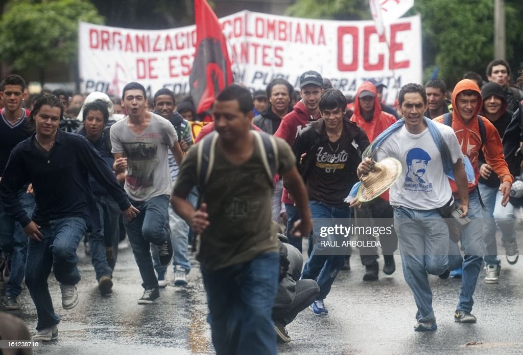 Students run during a protest in Medellin, Antioquia department, Colombia on March 21, 2013, demanding a better and free education and an alternative university reform . AFP PHOTO/Raul ARBOLEDA