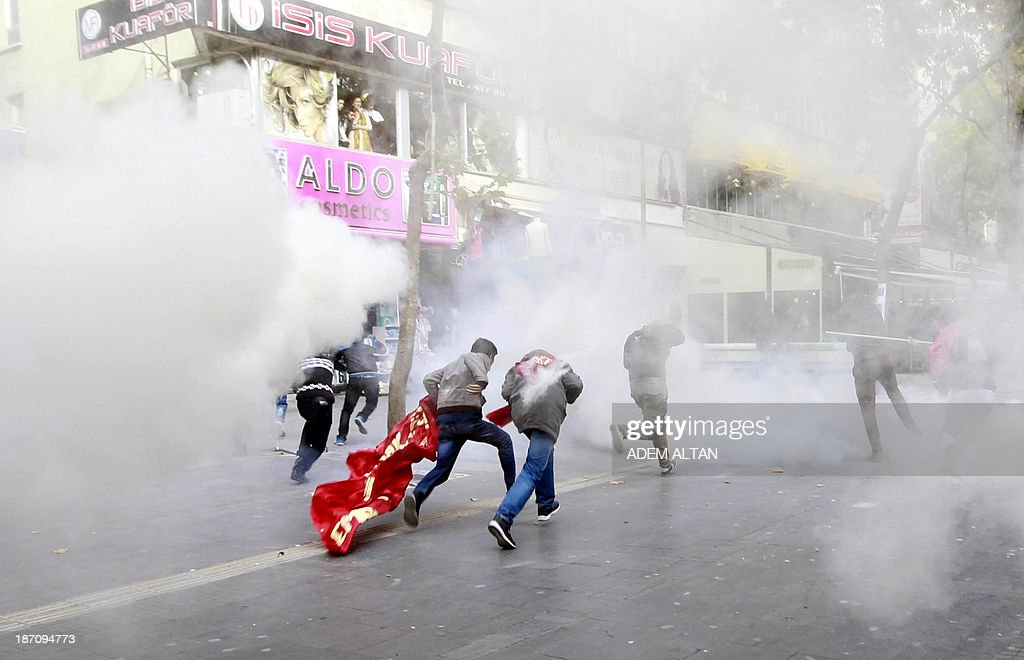 Students run in tear gas during a demonstration to protest against Turkey's High Educational Board (YOK) in Ankara, November 6, 2013.