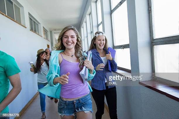 Students running down hallway, laughing
