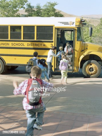Students (5-7) running on to school bus (blurred motion) : Stock Photo