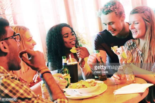 Students sat around table in restaurant eating and drinking