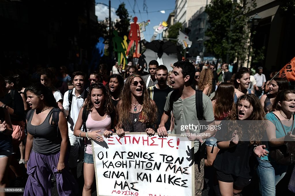 Students shout slogans during a demonstration in central Athens on September 18, 2013. As part of the controversial redeployment plan in the country reeling from six years of recession, civil servants have to accept new posts or spend eight months on reduced salaries as alternative posts are found, with the risk of losing their jobs altogether. The banner reads 'Wake up, the concerns of our teachers are also ours.'