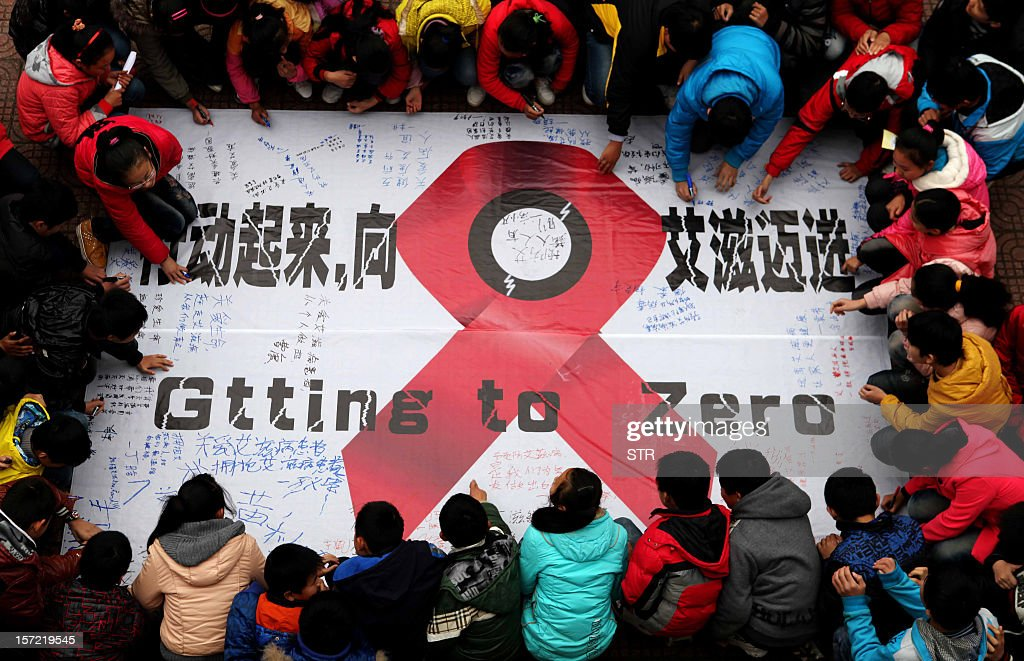 Students sign their names on an anti-AIDS banner during a AIDS day event at a school in Hanshan, central China's Anhui province on November 30, one day before the 2012 AIDS day. Chinese AIDS activists on November 29 accused the Communist Party's new number two Li Keqiang of hypocrisy after he called for more non-government efforts to fight the disease. CHINA OUT AFP PHOTO / AFP / STR