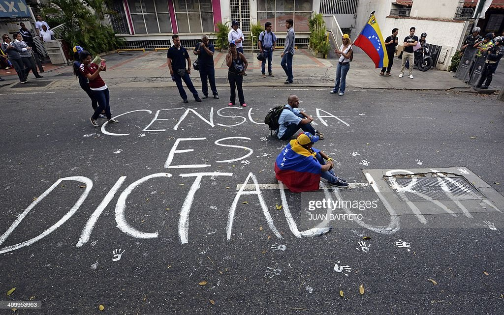 Students sit on the pavement reading 'Censorship is dictatorship' during an antigovernment protest in Caracas on February 17 2014 Venezuelan...