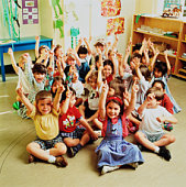 Students (4-6) sitting on floor with hands raised