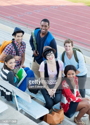 Students sitting together on bleachers : Stock Photo