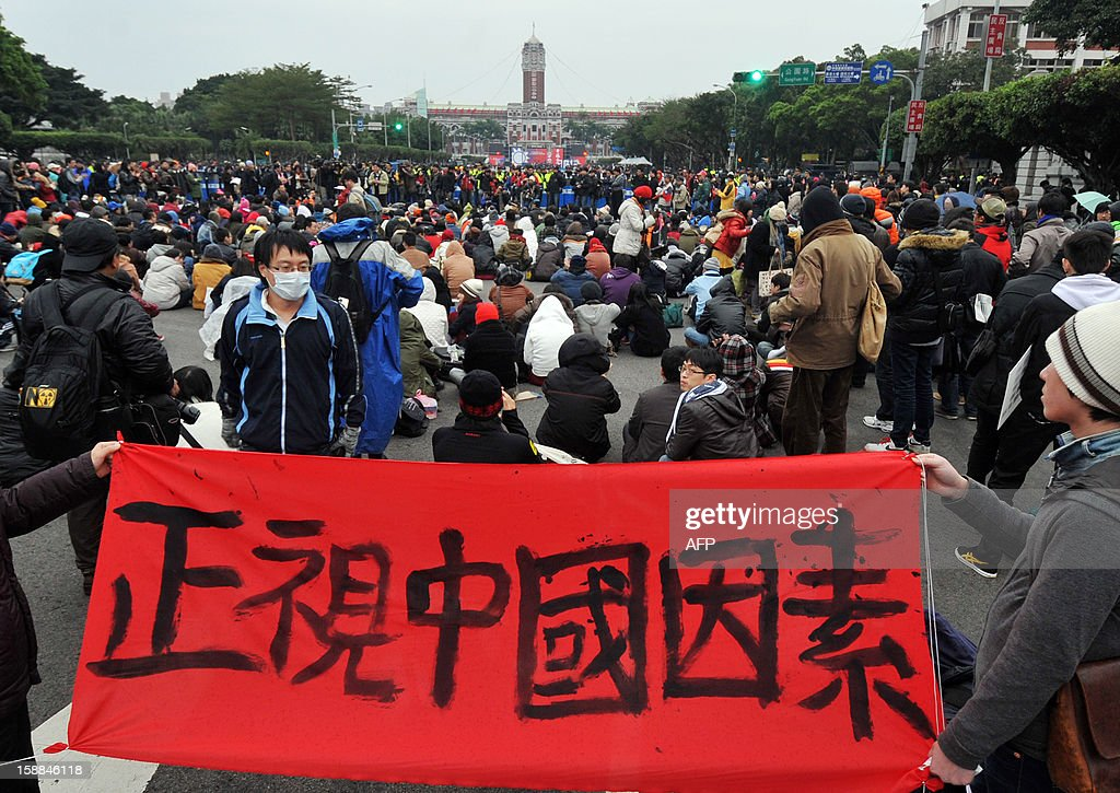 Students stage a sit-in protest and display a banner reading 'Face up to the China factor', as they attend a flag-raising ceremony on New Year's Day at the Presidential Office Square in Taipei on January 1, 2013. Student groups called on Taiwan's President Ma Ying-jeou to object to the planned sale of Hong Kong-based Next Media's Taiwan assets which they fear could create a pro-China media monopoly. AFP PHOTO / Mandy CHENG