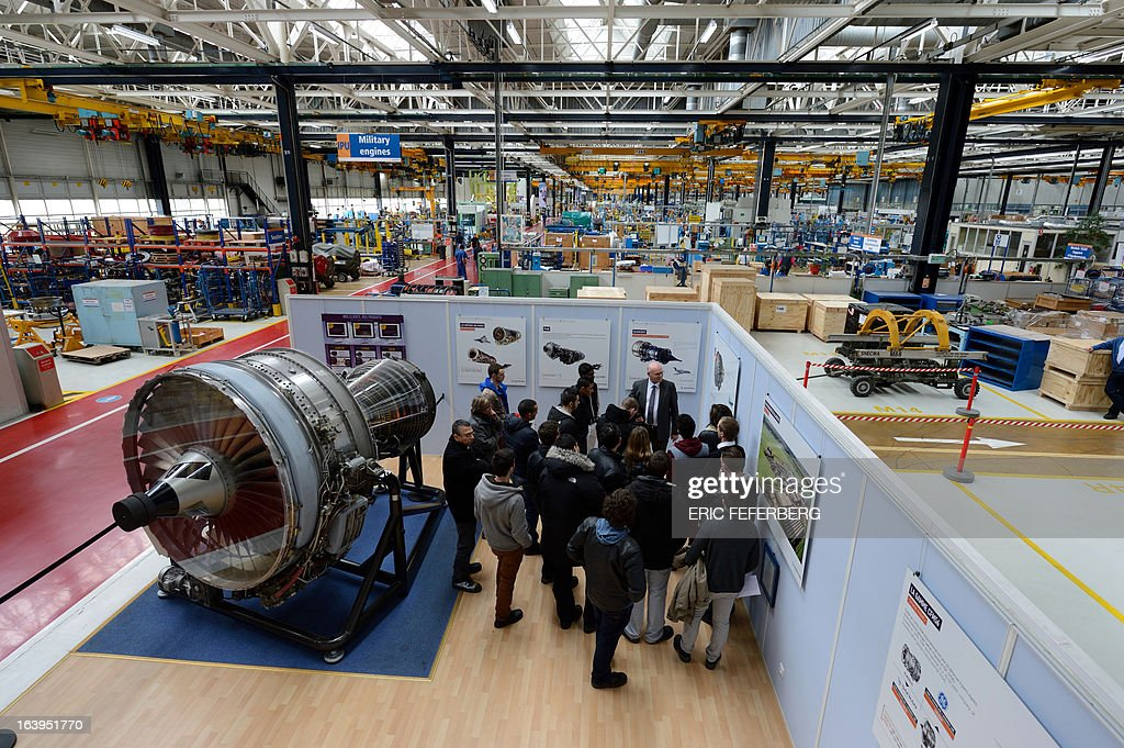 Students stand beside a jet engine as they visit the assembly halls of French aerospace and defence group Safran, manufacturing engines for commercial and military aircraft, on March 18, 2013 at the SNECMA Villaroche site in Moissy-Cramayel, south east of Paris. AFP PHOTO ERIC FEFERBERG