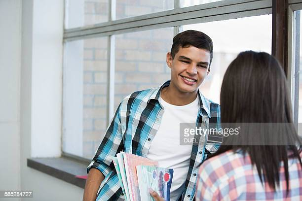 Students standing by window, chatting