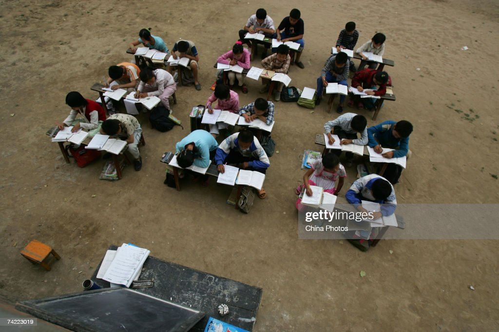 Students study outdoors at a countryside primary school May 22, 2007 in Huxian County of Shaanxi Province, China. Class is held outdoors for safety due to the schoolhouse being in danger of collapsing. In some rural areas of China, education still faces a lack of funding, good teachers and stable facilities.