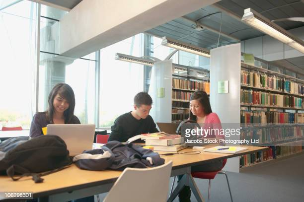 Students studying at library table