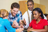 Students studying brain educational model with teacher in class