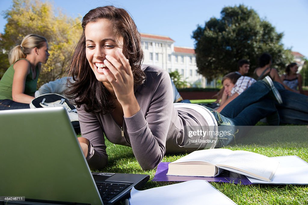 Students studying outdoors with laptop : Stock Photo