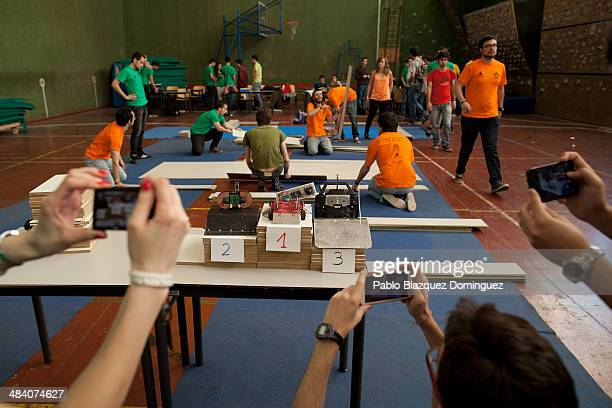 Students take pictures of the podium after Carlos Hucha won the sumo robots combat contest during the Cybertech robotics competition at the the...