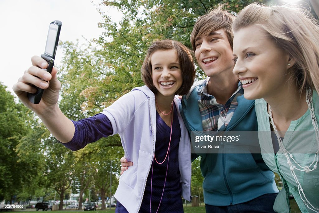 Students taking picture with camera phone : Photo