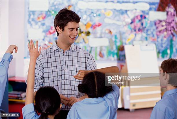 Students taking turns answering teacher's question in class