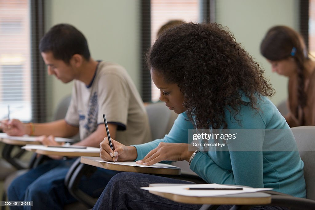 Students taking written examination, side view : Stock Photo